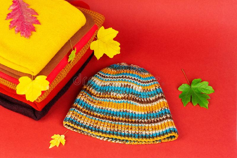 Pile women clothing, warm autumn clothes and knitted hat with colorful autumn maple leaves on a red background, a close-up. View from above royalty free stock images