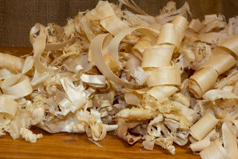 Wood Shavings. Pile of Wood Shaving Curls on finished wood with burlap background royalty free stock photo