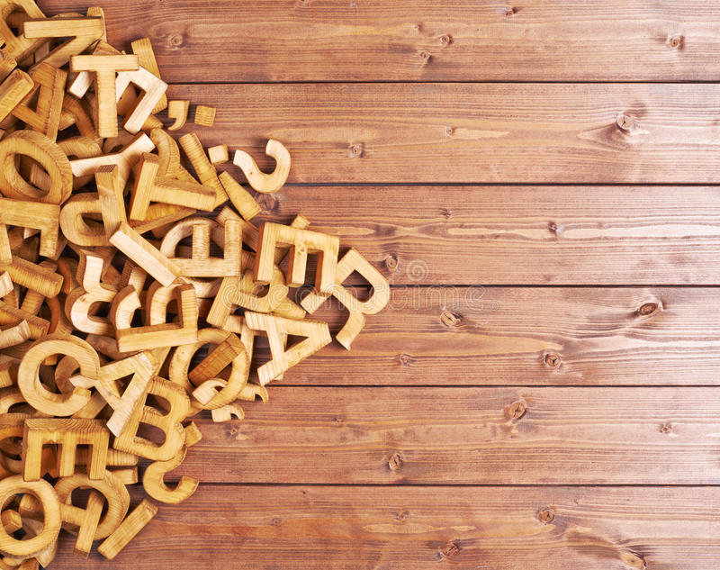 Pile of wooden letters. Over the surface of the brown wooden boards royalty free stock photography