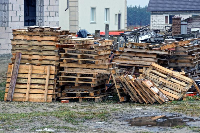 A pile of gray old wooden pallets on the street in the yard near the house. A pile of wooden pallets in the yard near the house royalty free stock photos