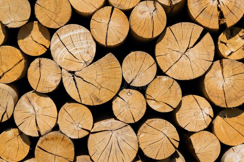 Pile of worked wooden roundish clear beautiful logs, stacked firewood royalty free stock photography