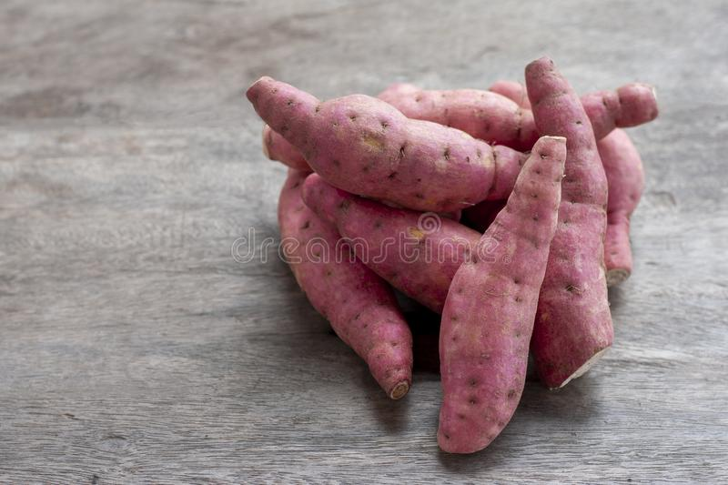 Pile of Yam or Sweet potato on wooden table. royalty free stock images