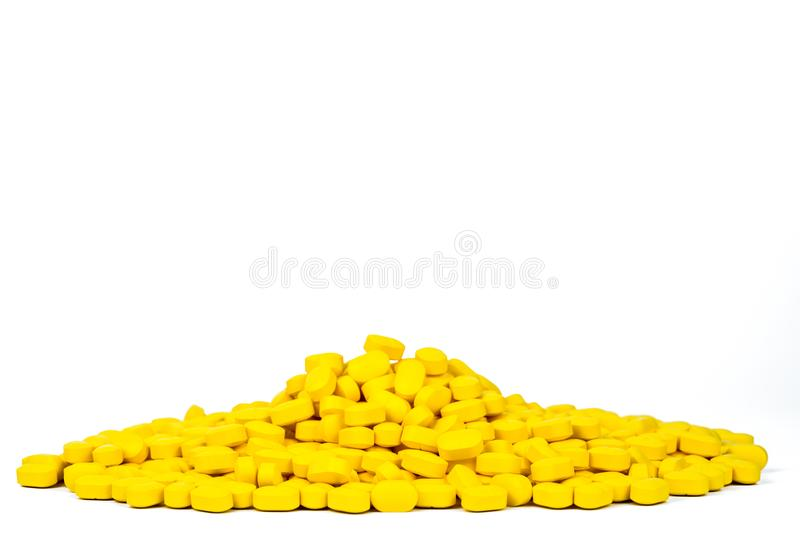 Pile of yellow ovoid-rectangular shape tablet pills isolated on white background with copy space. Medicine for relief pain. And migraine headache royalty free stock photography