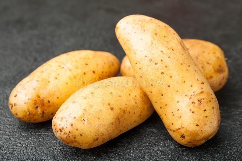 A pile of young potatoes on a black background royalty free stock photos