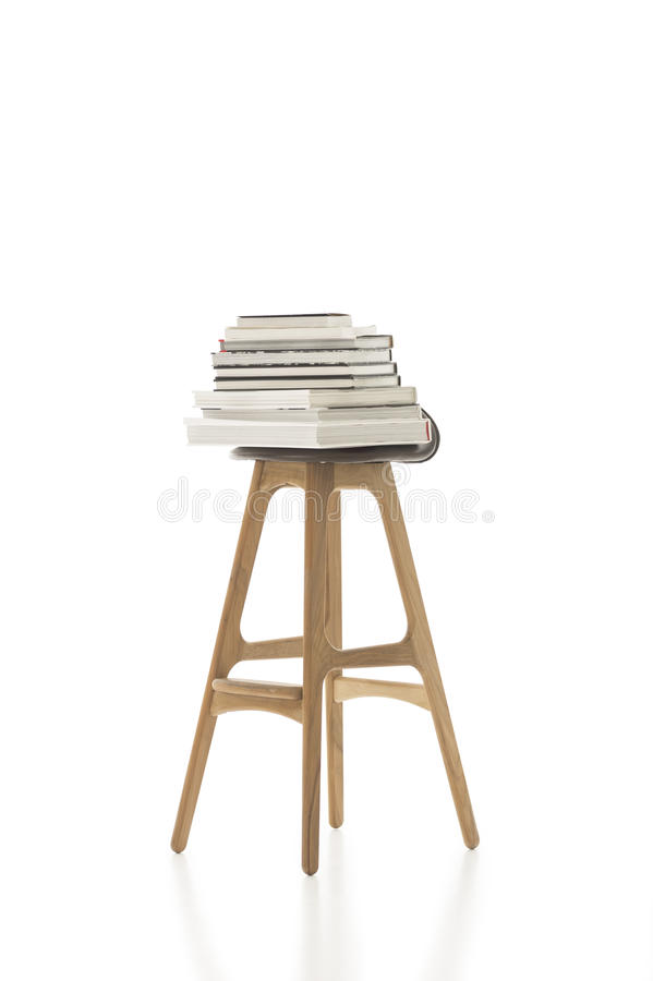 Piled Books on Top of Tall Single Chair. Conceptual Piled Books on Top of Tall Single Chair, with Wooden Legs, Isolated on White Background. Emphasizing Copy stock photography