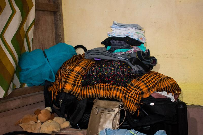 Piled and Dumped Newly Washed Clean Clothes, Bags, Blankets and Toys in A Corner of the Room. A newly washed clean clothes, blankets, pillow covers and bags stock photo