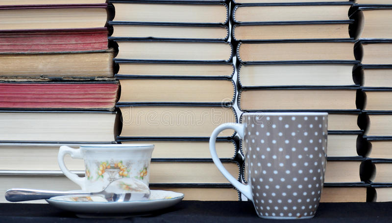 Piled new and old books. Cups royalty free stock photos