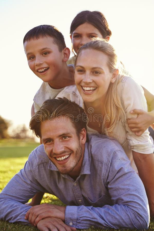 Free Piled Up Happy White Family Lying On Grass Looking Away Royalty Free Stock Image - 99965466