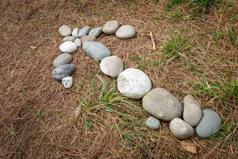 Pilen som ut läggas med stenar, visar riktningen av rörelse för det folk som borttappat deras väg i skogen fotografering för bildbyråer