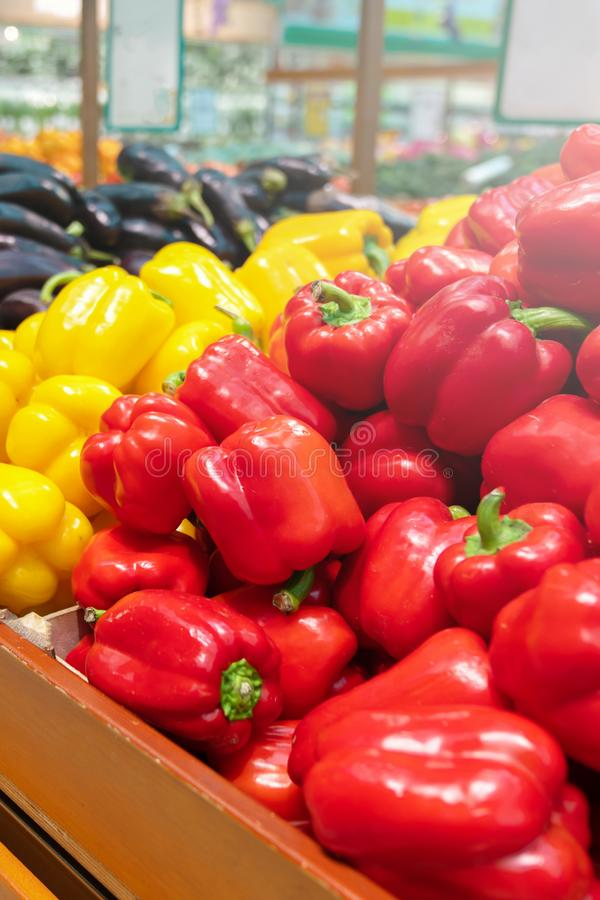 Piles of bell peppers organized at the counter of a supermarket or grocery store. red, orange and yellow bell peppers royalty free stock photos