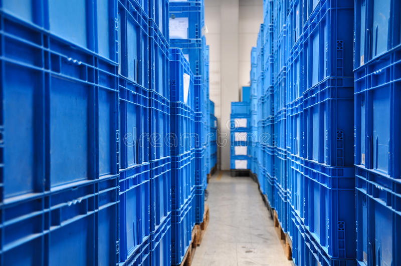 Piles of blue plastic containers in a warehouse in Germany. The boxes are used in the logistics chain transporting the produced goods.Selective focus on the royalty free stock photos
