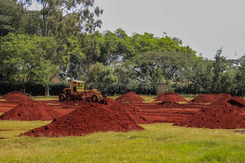 Piles of bright, saturated and oily red soil on a field with a tractor in Nairobi. Kenya stock images