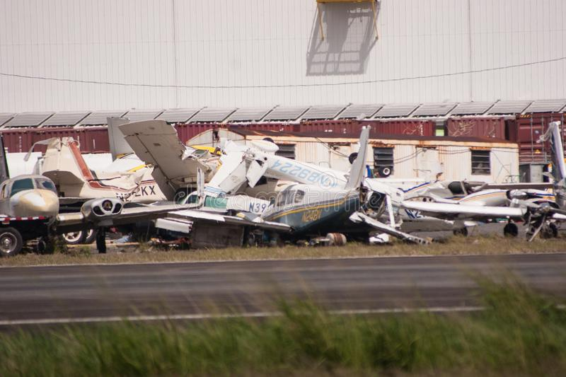 The wreckage of Hurricane Maria. Piles of broken planes that were blown into each other during Hurricane Maria sit aside the runway at the airport, on November royalty free stock images