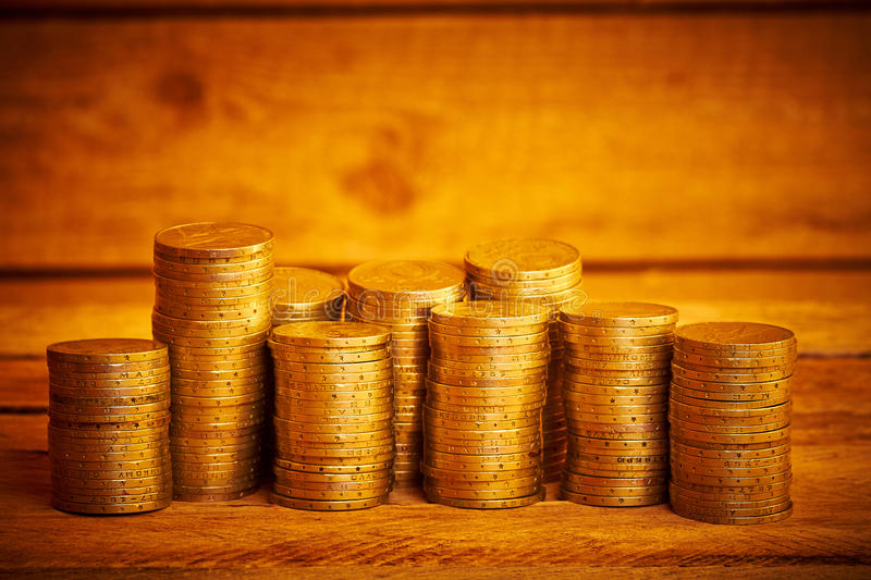 Piles of coins. Piles of old coins on the wooden table royalty free stock photography