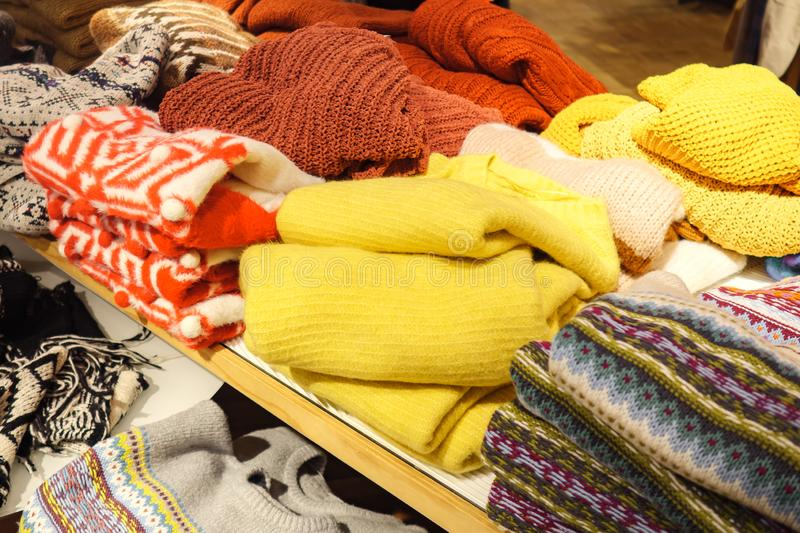 Piles of colorful sweaters on shelf royalty free stock photography