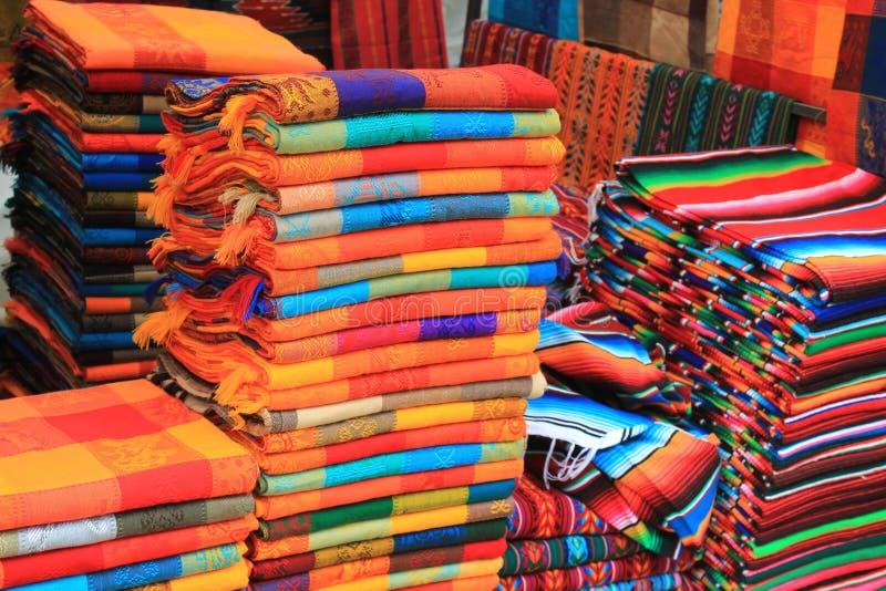 Colorful woven fabric at a Mexican craft market. Piles of colorful woven fabric at a craft market in San Cristobal de las Casas, Chiapas, Mexico stock images