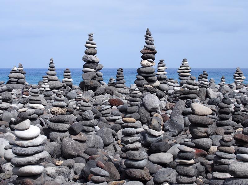 Piles d'art de roche et tours des pierres et des cailloux gris sur une plage image libre de droits