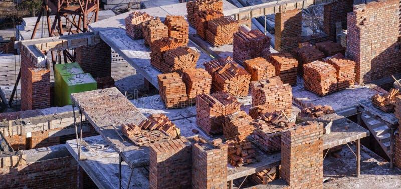 Piles de briques sur le chantier de construction d'un bâtiment à plusiers étages photo stock
