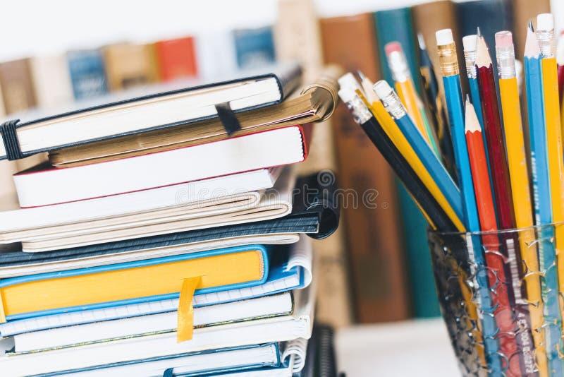 Piles de carnets, pile d'éducation de livres de nouveau au fond d'école, manuels et crayons dans le support en plastique avec l'e image stock