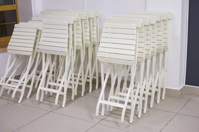 Piles de chaises pliantes blanches dans le bureau photographie stock