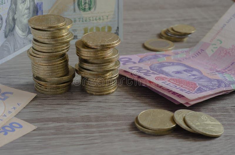 Piles de hryvnia ukrainien de pièces de monnaie et de dollars US photos libres de droits