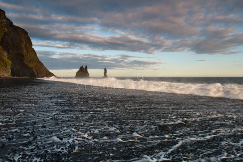 Piles de mer et basalte Clifs à l'est de la plage de sable de noir de Reynisfjara image libre de droits