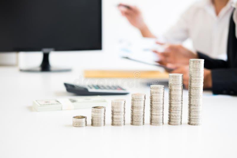 Piles de personne de pièces de monnaie dirigeant des buts de finances d'écriture sur le calcul photographie stock