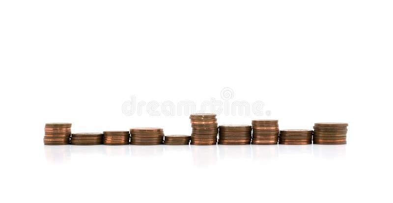 Piles de pièces de monnaie en cuivre dans une ligne d'isolement sur le blanc images stock