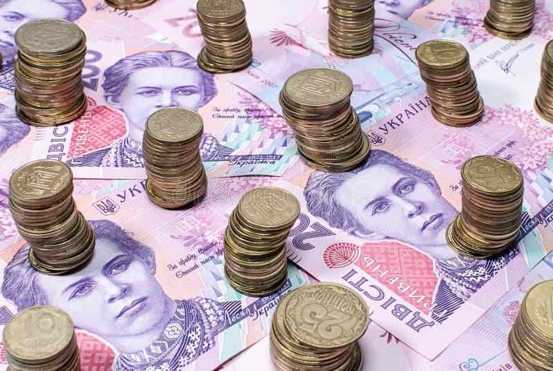Piles de pièces de monnaie sur les billets de banque deux cents hryvnias ukrainiens photo stock