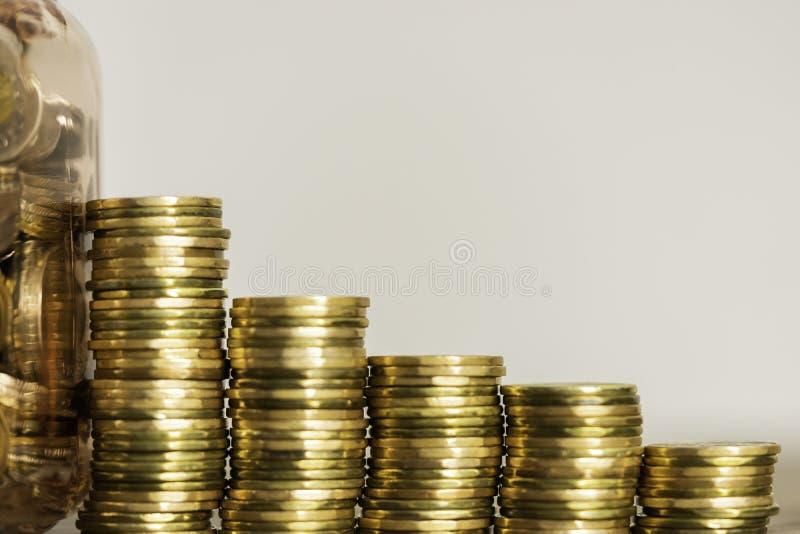 Piles de pièces de monnaie à côté d'un pot complètement de pièces de monnaie image libre de droits
