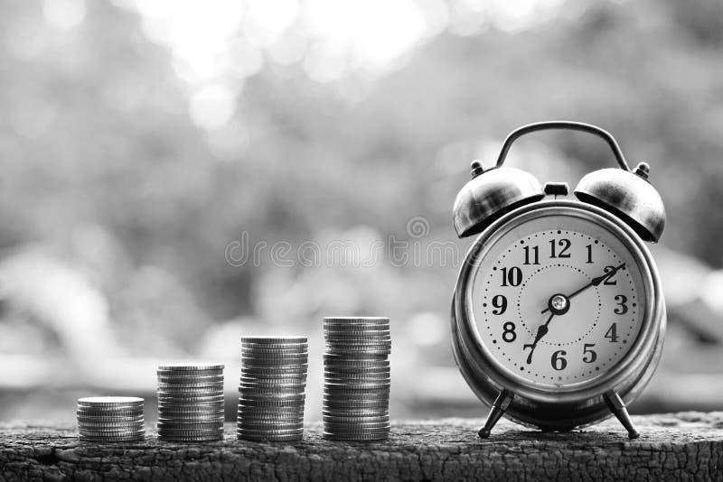Piles de réveil et de pièce de monnaie sur la table en bois avec le fond vert de jardin de tache floue, le ton lumineux de couleu images stock