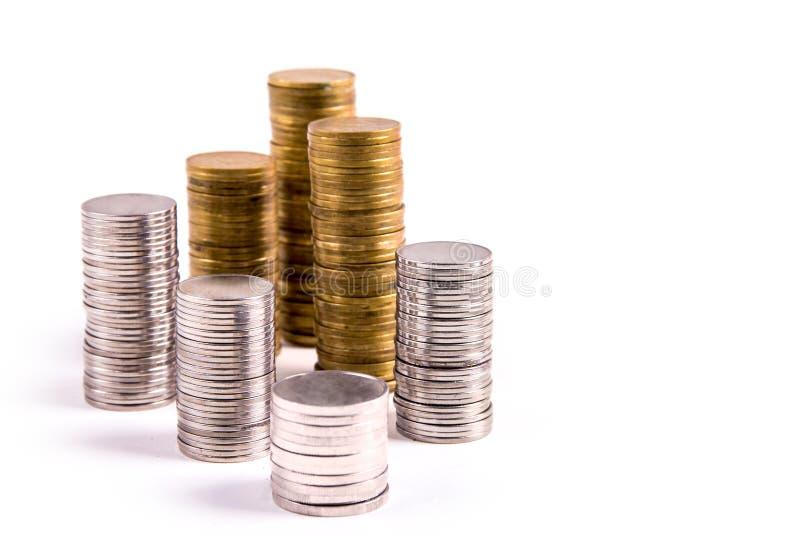 Piles des pièces d'or et en argent d'isolement photos stock