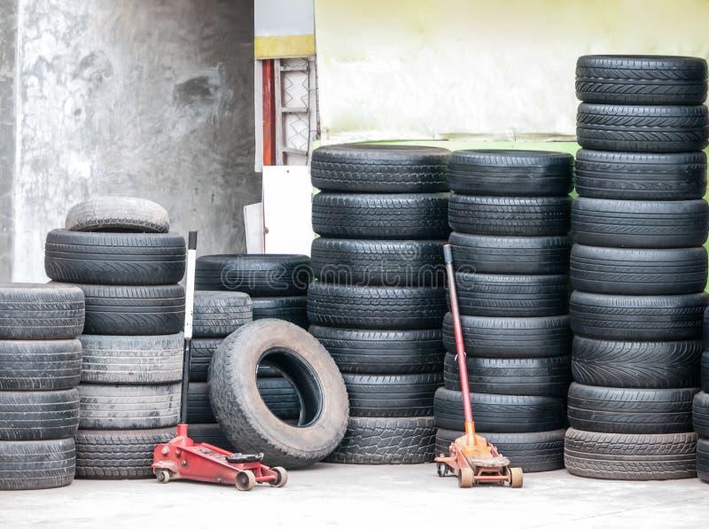 Piles des pneus de voiture d'occasion et du cric hydraulique de plancher images libres de droits