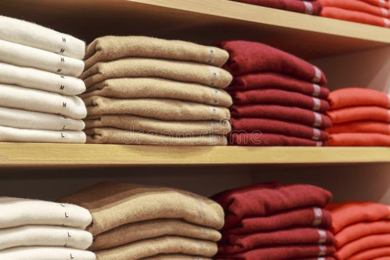 Piles des vêtements multicolores sur les étagères dans le magasin images libres de droits
