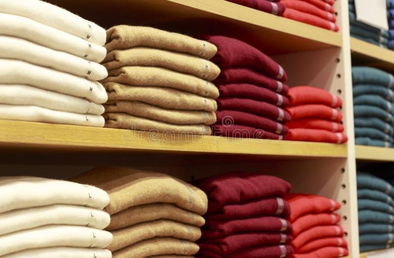 Piles des vêtements multicolores sur les étagères dans le magasin photo libre de droits