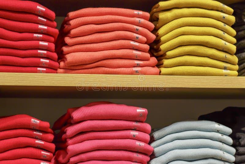 Piles des vêtements multicolores sur les étagères dans le magasin photographie stock