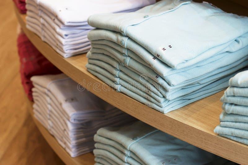 Piles des vêtements multicolores sur les étagères dans le magasin photos libres de droits