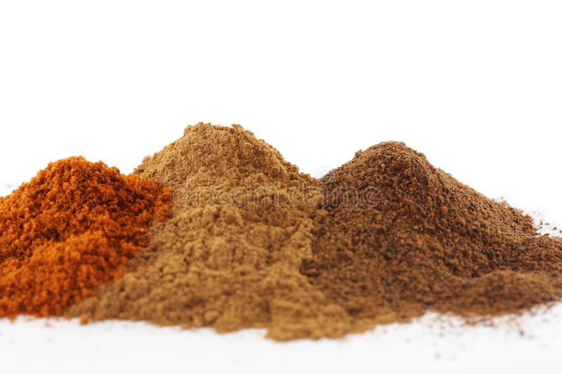 Piles of different colourful spices, copyspace. Small piles of various spices for cooking, isolated on white with copyspace stock photo