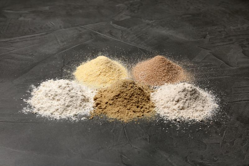 Piles of different flour types. On grey table royalty free stock images