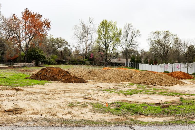 Piles of dirt hauled into vacant residential lot in early spring to prepared for construction.  stock photography
