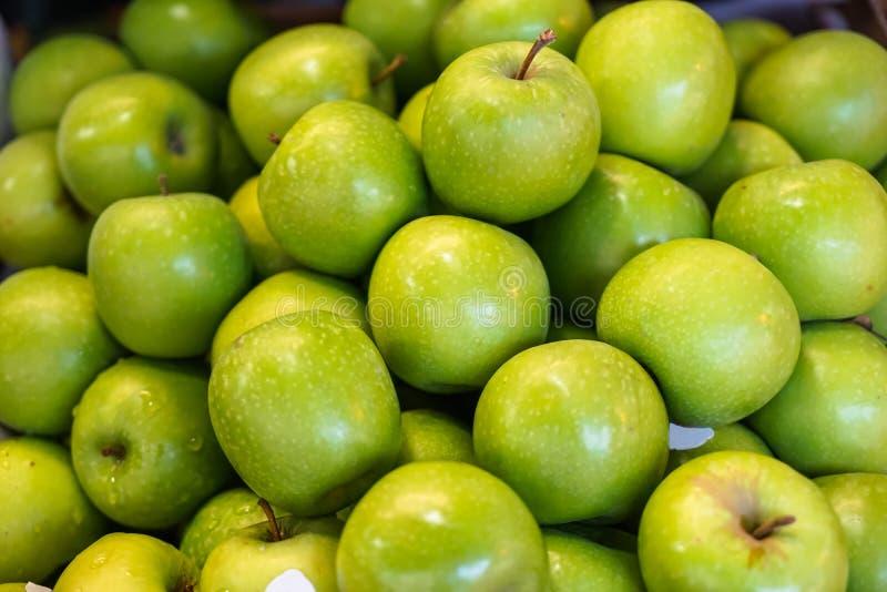 Piles du beau fond vert clair délicieux abondant frais de fruit de pomme se vendant sur le marché local image stock