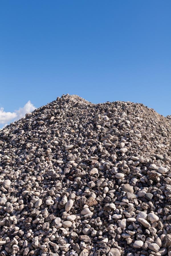 Piles du gravier au chantier de construction sous le ciel bleu lumineux photographie stock libre de droits