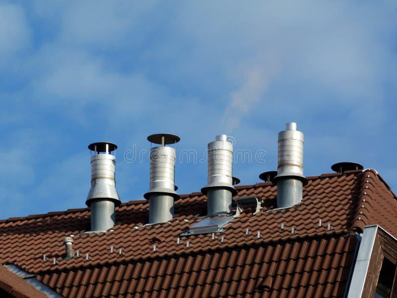 Piles en aluminium sur le toit de tuile brun d'argile sous le ciel bleu images libres de droits