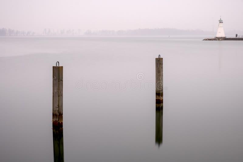 Piles et phare dans l'eau calme photographie stock