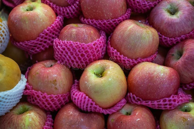Piles of fresh abundant beautiful delicious gradient red apple fruit in pink foam wrap selling in local market stock image