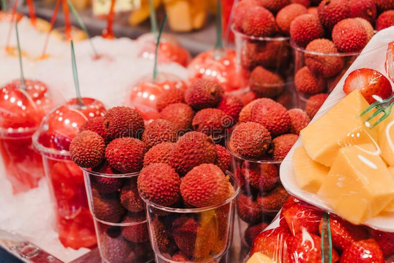Piles of fresh lychees for sale at a market stall in portions plastic cup. royalty free stock images
