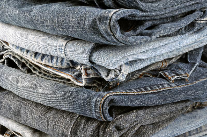 Piles of jeans folded in close up. Canvas jeans pants folded in close-up royalty free stock image