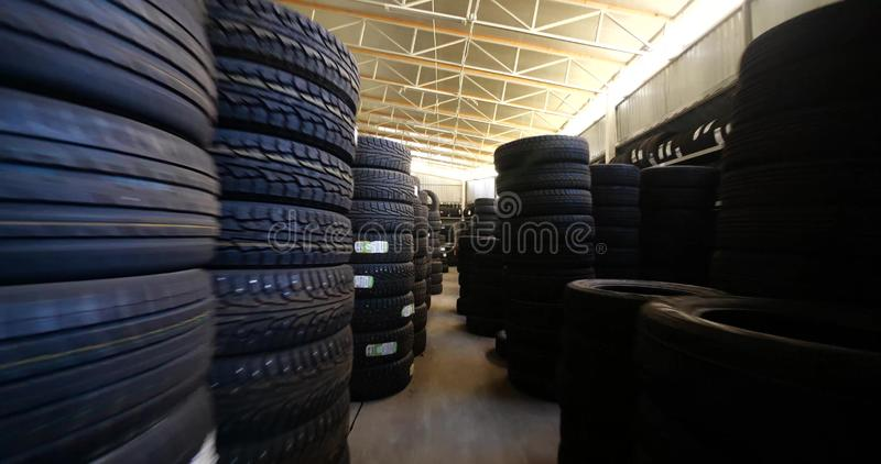 Piles of new tires in tyre warehouse in car garage. Piles of new tires in a tyre warehouse in car garage royalty free stock images
