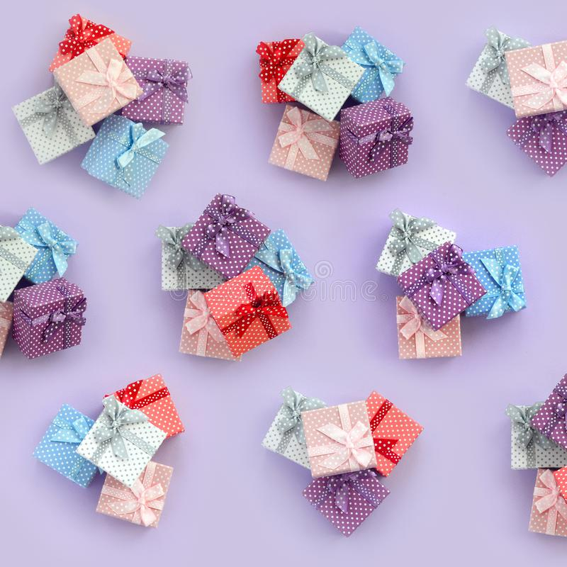 Piles of a small colored gift boxes with ribbons lies on a violet background. Minimalism flat lay top view pattern royalty free stock photos