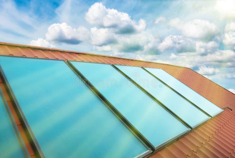 Piles solaires sur le toit rouge de maison photographie stock